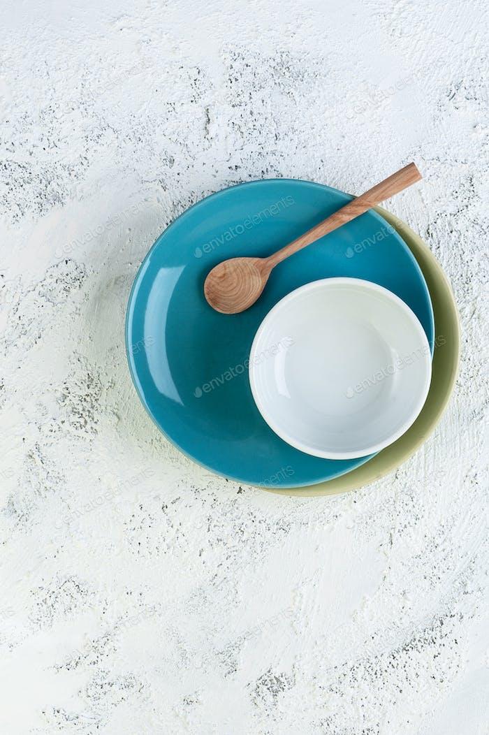 Dos platos, un tazón y una cuchara de De madera en una textura gris claro b