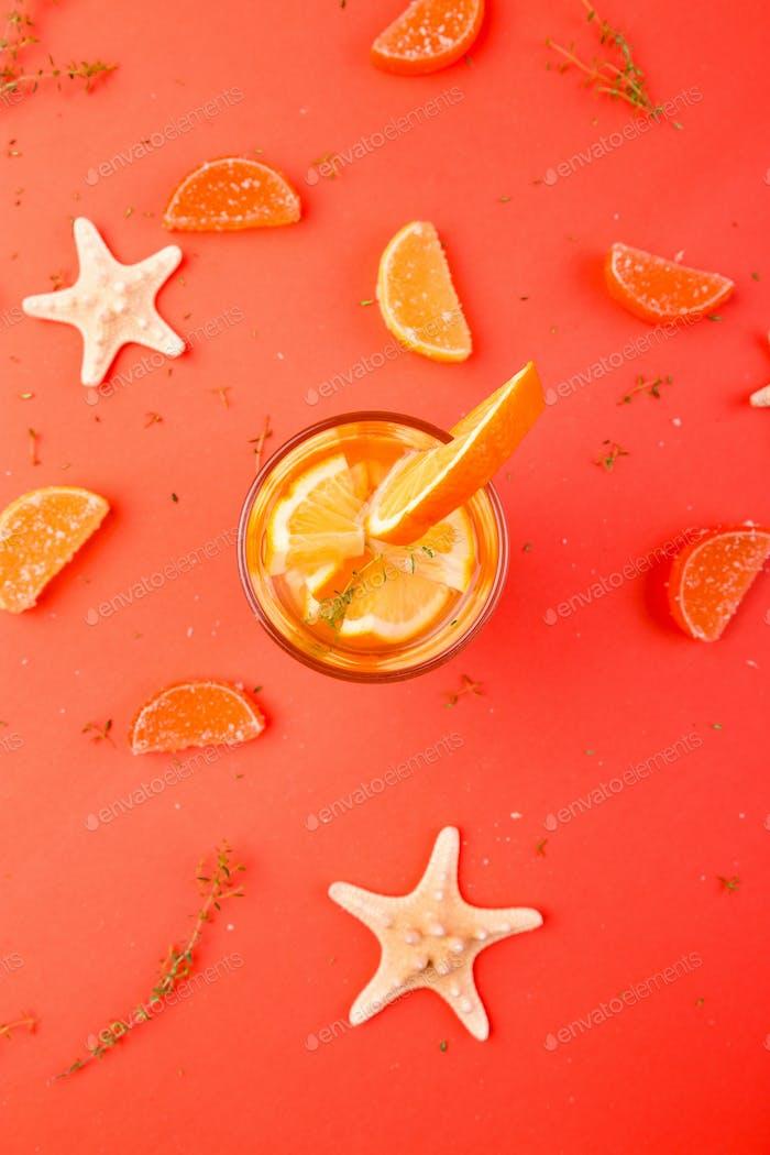 Orange fruit cocktail, detox water on orange background.