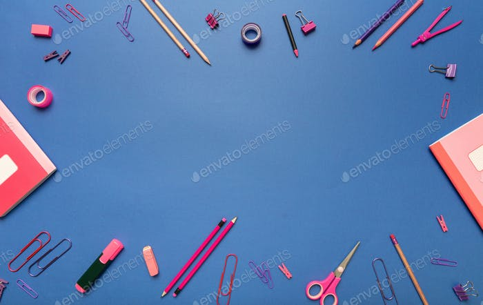 Flat lay of school stationery, pink color on blue background