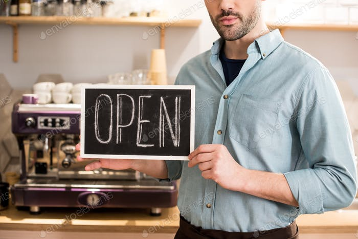 partial view of barista with open blackboard in hands in coffee shop