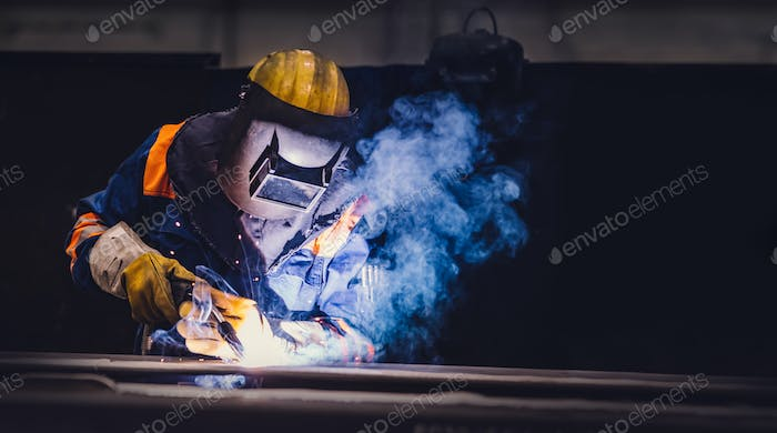Worker welding in a factory.