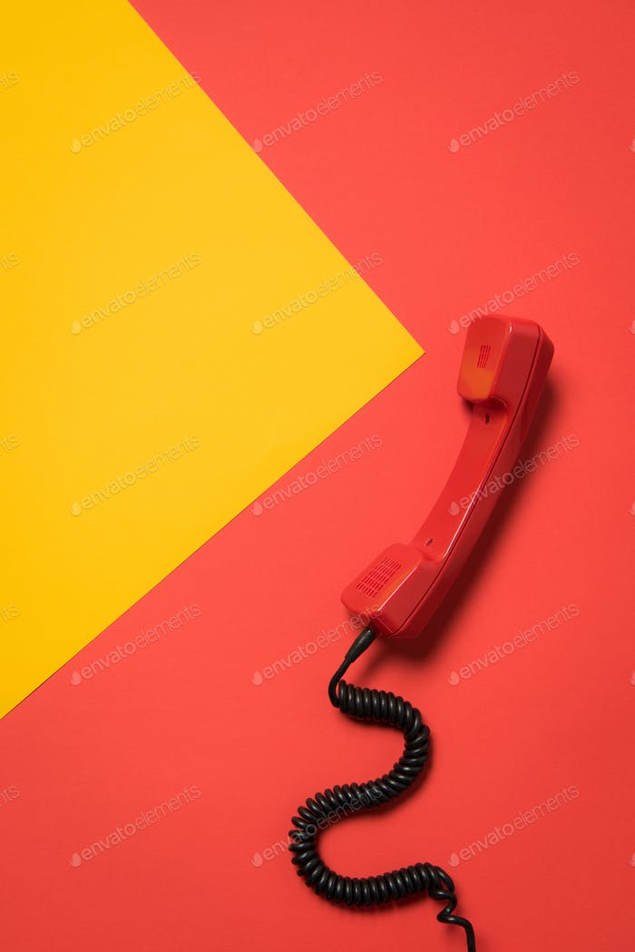 Close-up view of red telephone receiver with curly cord, communication concept