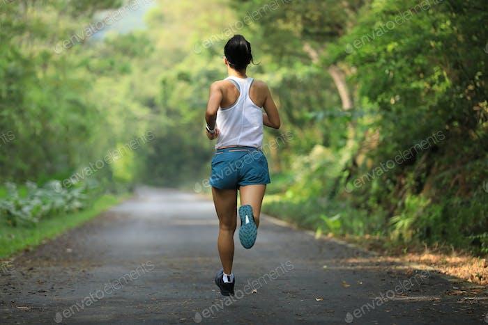 Fitness woman runner running on summer park