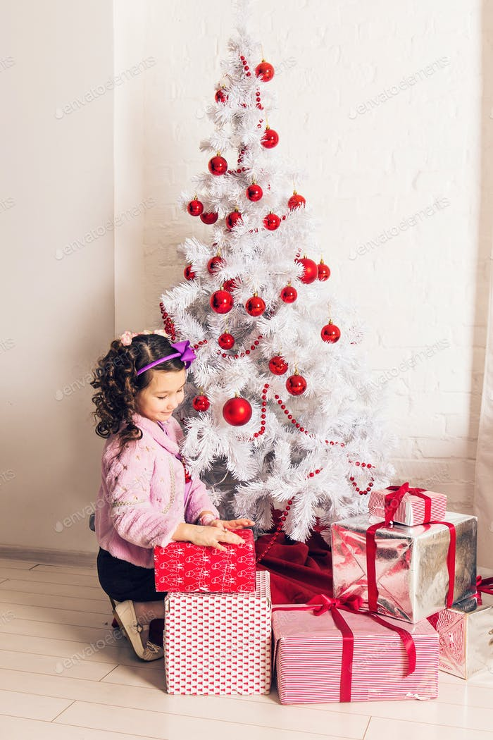 Child with gift box near white Christmas tree