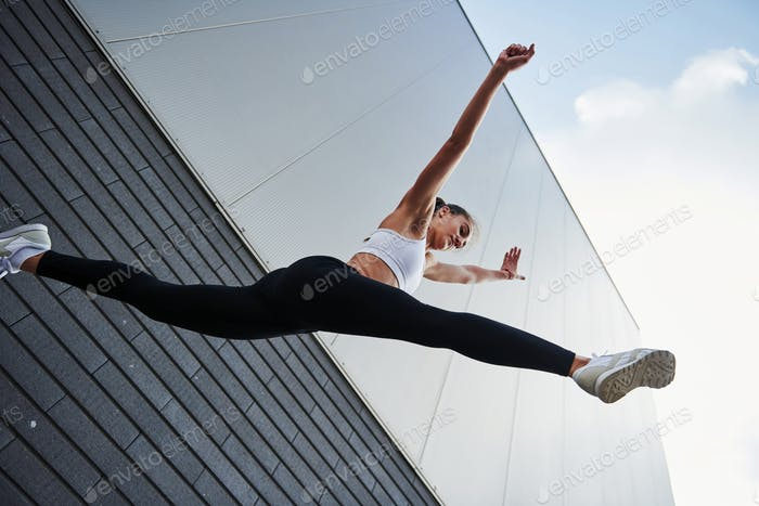 Bottom view. Young sportswoman doing parkour in the city at sunny daytime