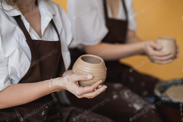 Two women make pottery on a pottery wheels, shaping clay by their hands, close up. Pottery craft