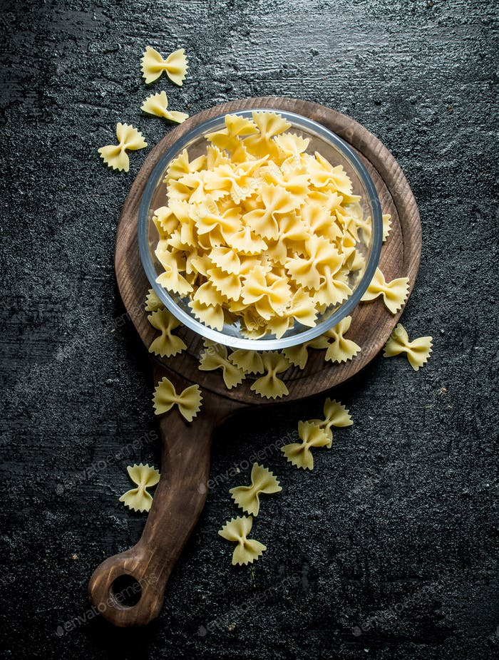 Dry Farfalle pasta in a glass bowl on a cutting Board.