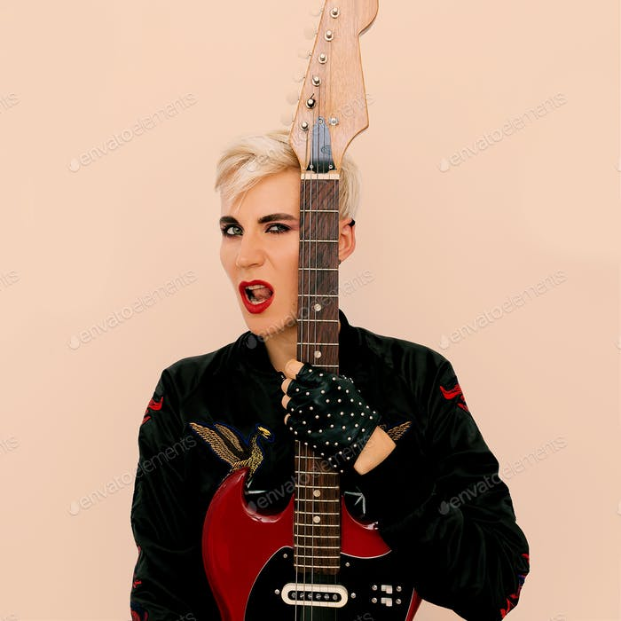Tomboy fashion Model with electro guitar. Rock style