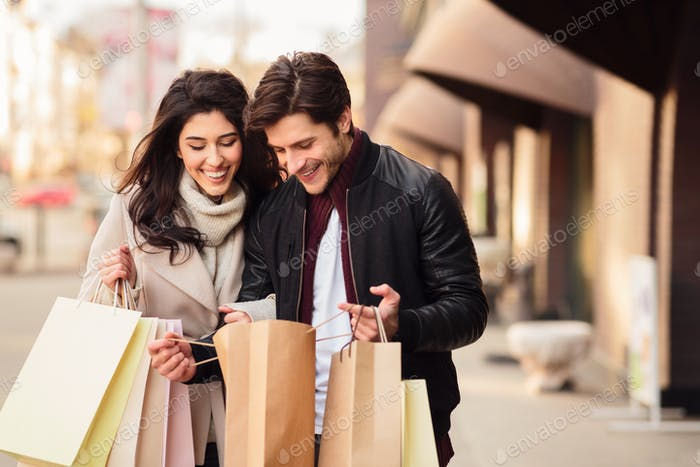 Excited couple looking into shopping bags outdoors