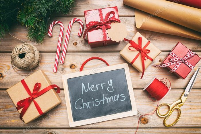 Christmas gift boxes wrapping and a blackboard on wooden background, merry christmas text, top view