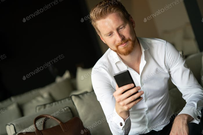 Young happy attractive business man using smartphone