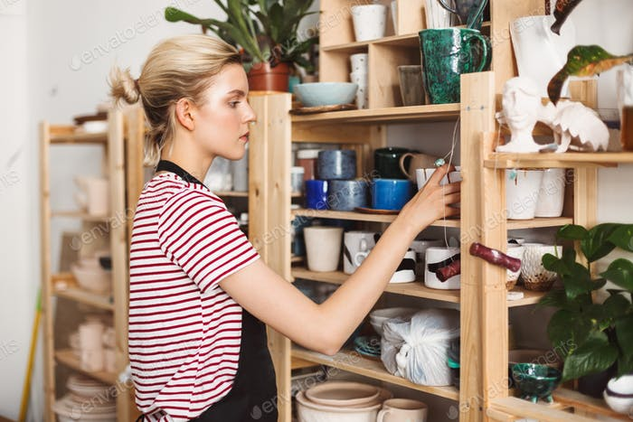 Girl in black apron and striped T-shirt thoughtfully putting handmade dishes on shelves at pottery