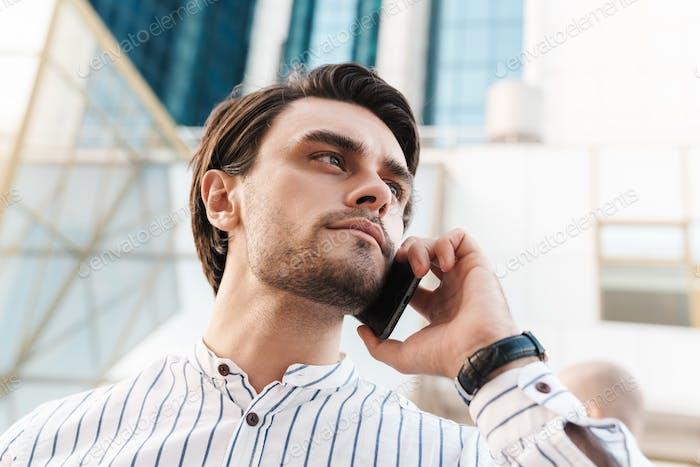 Foto eines ernsthaften jungen Mannes, der auf dem Handy spricht und beiseite schaut, während man auf der Stadtstraße spaziert