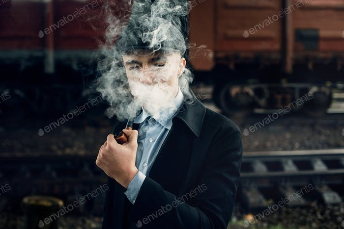 Stylish gangster smoking in tweed look, posing on background of railway