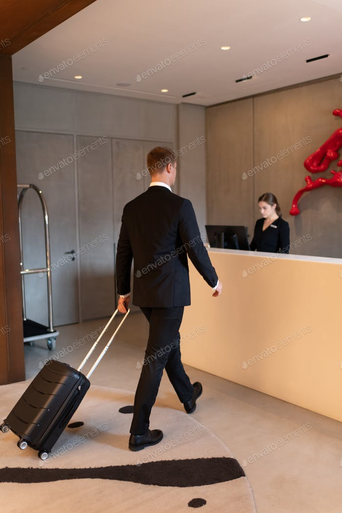 Businessman walking to reception for checkout in hotel