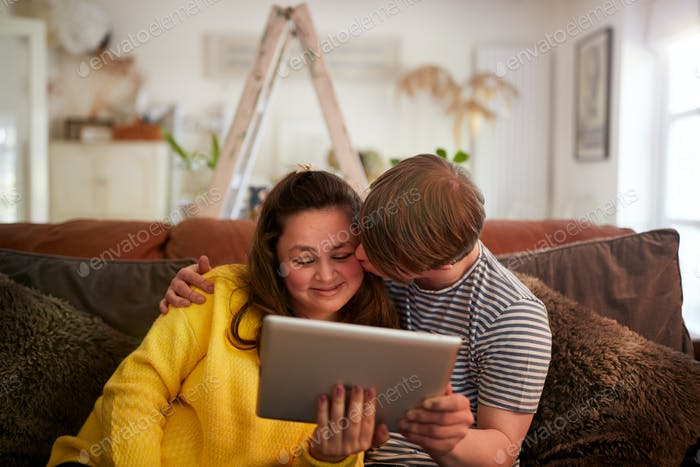 Loving Young Downs Syndrome Couple Sitting On Sofa Using Digital Tablet At Home