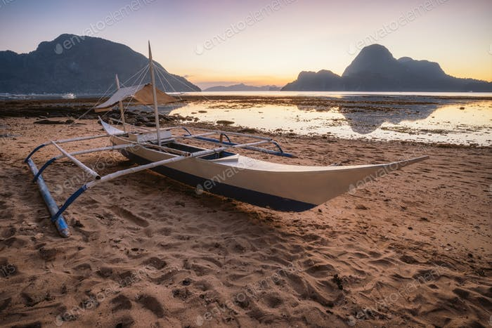 Palawan, Philippines. El Nido shore beach with local banca boat with picturesque sunset golden light