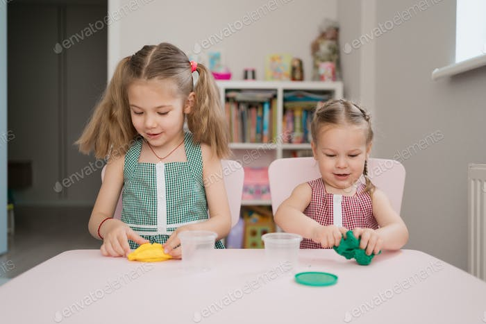 Cute little girls moulding from plasticine on pink table
