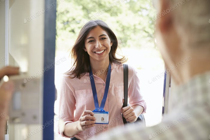 Senior man opening front door to young woman showing ID card