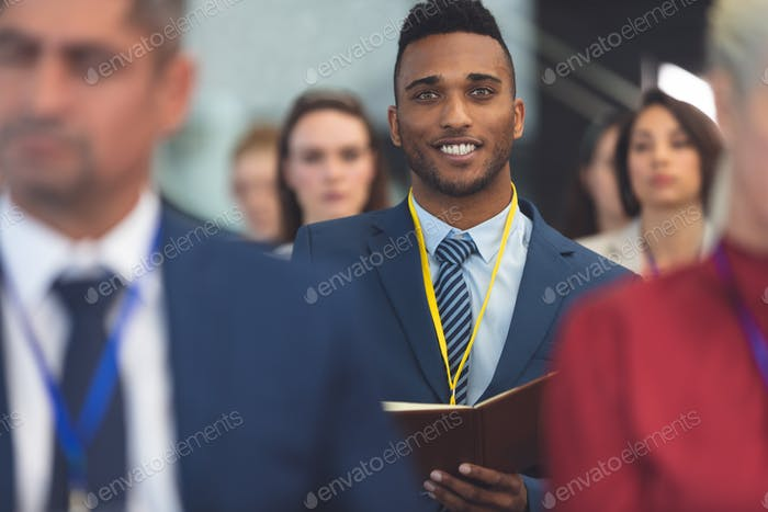 Businessman smiling at camera at business seminar in office building