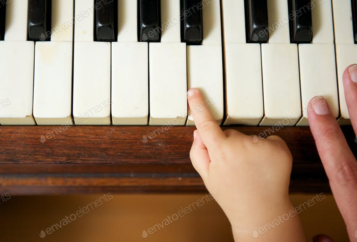 Baby hand playing piano with adult hand