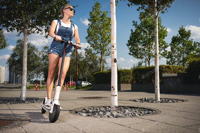 Junge Frau reitet auf Elektroroller