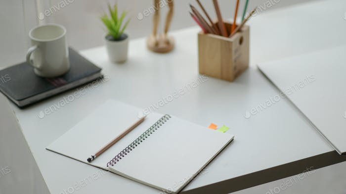 Open the notebook on the desk in a simple workspace complete with stationery and coffee.