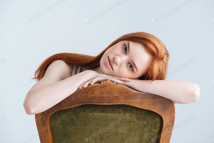 Relaxed redhead woman sitting on the chair