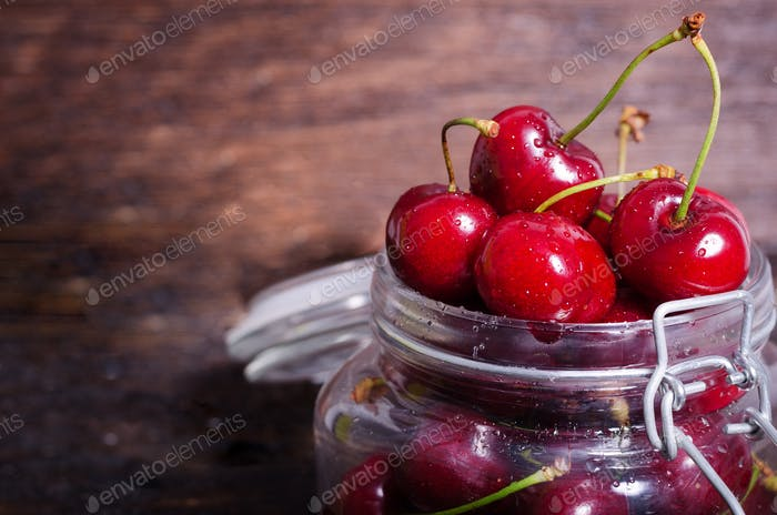 Big red cherries in a glass jar on dark wooden background with copy space. Summer and harvest