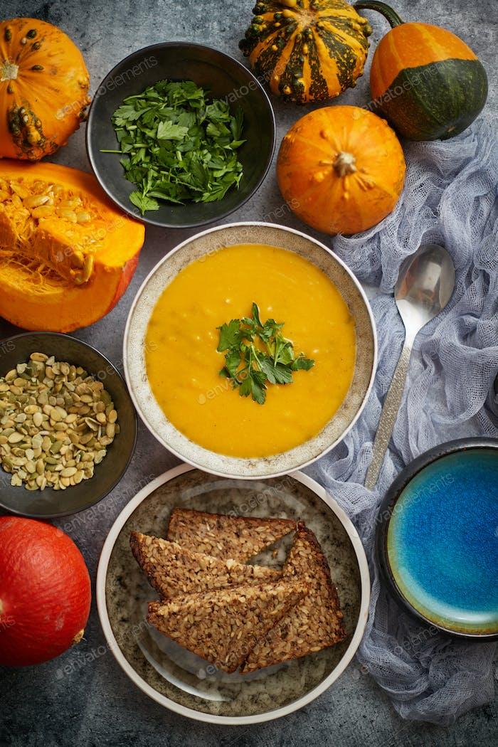Kürbissuppe mit Petersilie für Thanksgiving, Halloween dekoriert. Platziert auf grauen Steinhintergrund