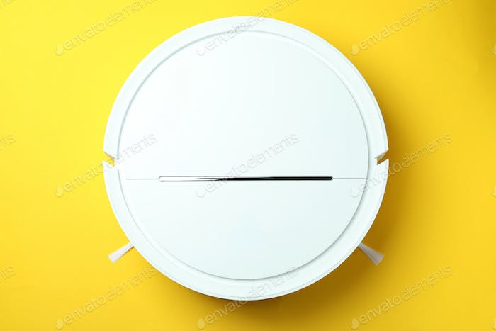 Robot vacuum cleaner on yellow background, top view