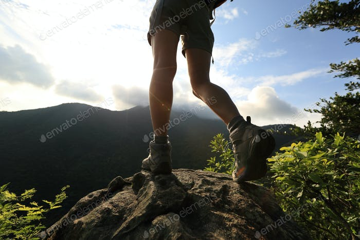 young hiker legs hiking on mountain peak