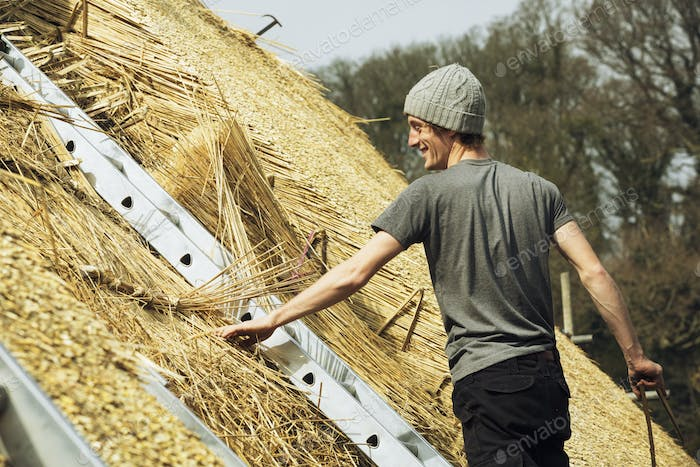 Young man thatching a roof, standing on a ladder.