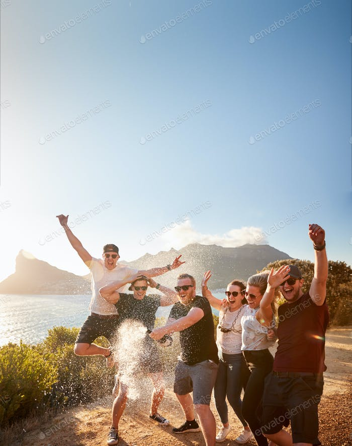 Six young adult  friends celebrating on a coastal path opening a bottle of champagne