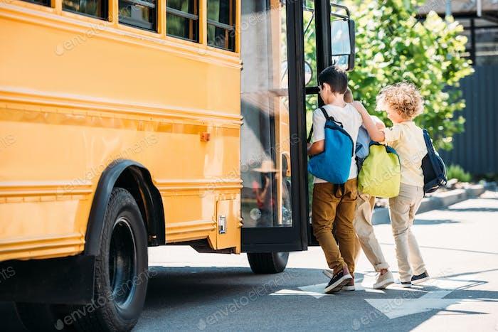 adorable little schoolboys entering school bus