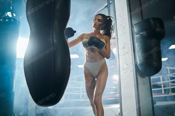 Fitnesswoman hitting punching bag