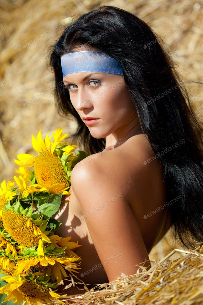 Young woman standing in dry hay and covering body with sunflowers