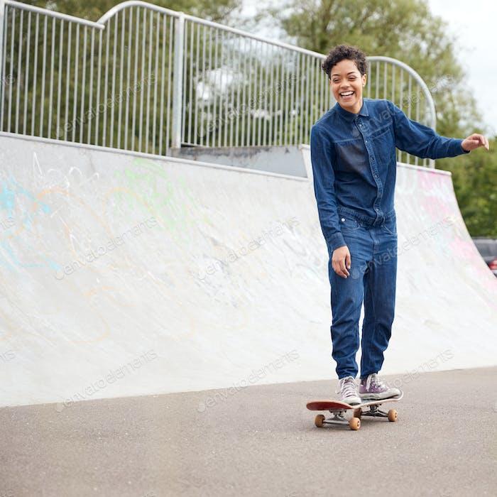 Weibliche Freunde mit Skateboards und Fahrrad Wandern durch Urban Skate Park
