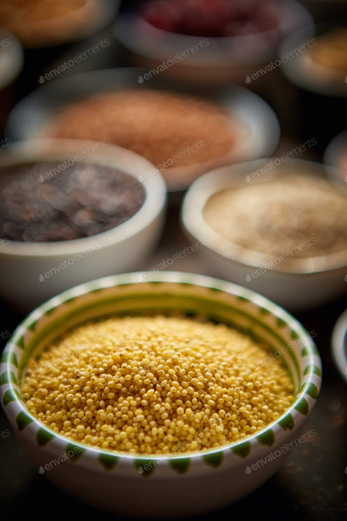 Raw couscous seeds in ceramic bowl. Selective focus