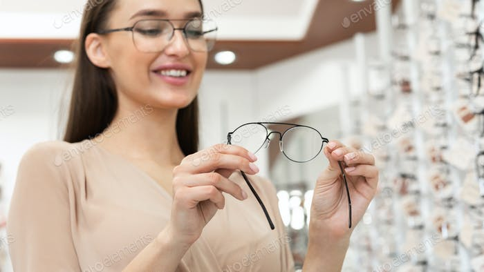 Portrait of smiling young woman choosing spectacles