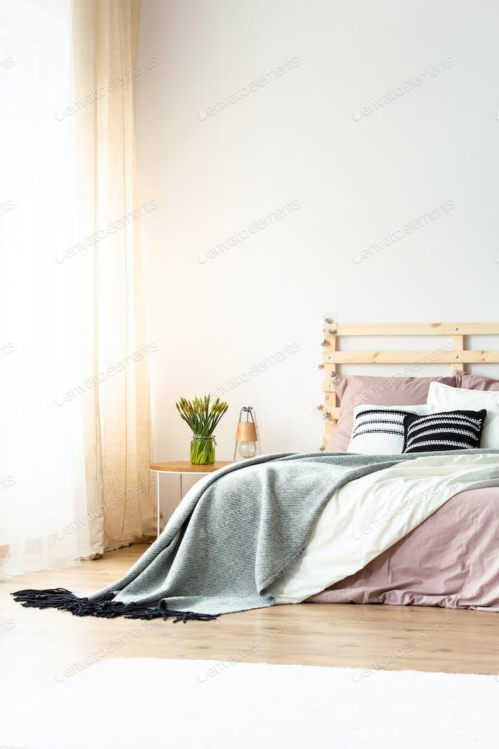 Grey blanket on pink bed with headboard in pastel bedroom interi