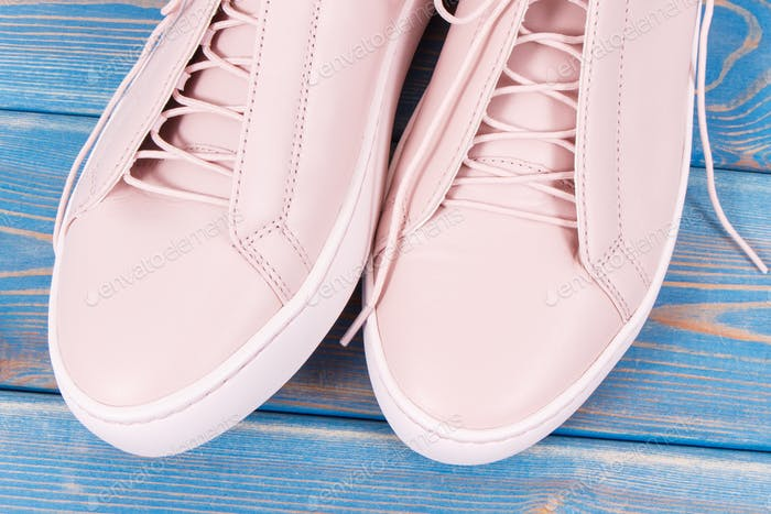 Pair of pink leather shoes for woman on old blue boards