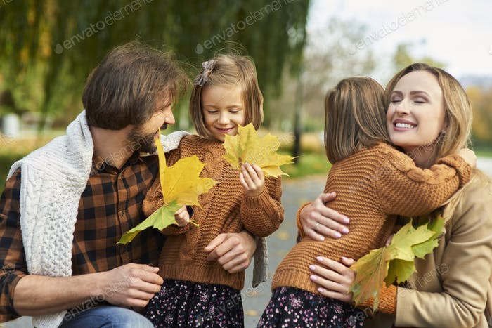 Cheerful scene of family in autumn forest