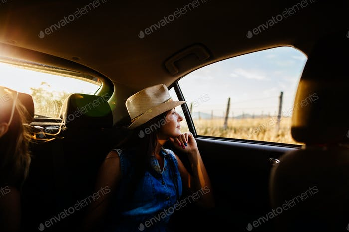 woman travel and dreaming by car with sunlight and picturesque view