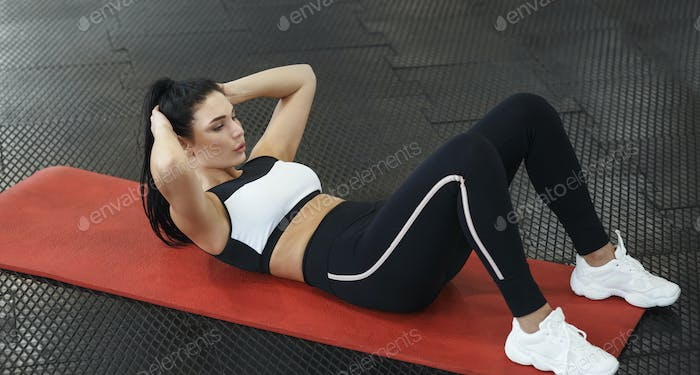 Attractive young woman doing abs exercises on yoga mat in gym