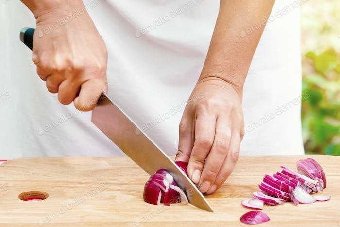 Female hands cut onions on wooden board
