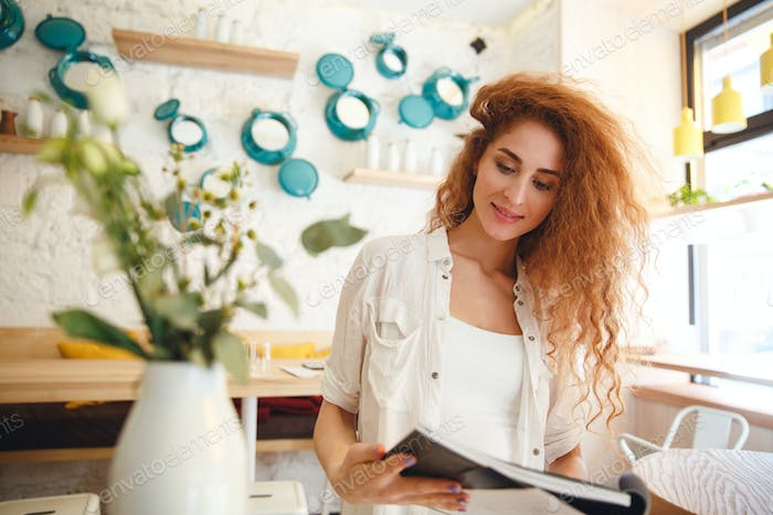 Gorgeous smiling redhead young lady standing in cafe reading