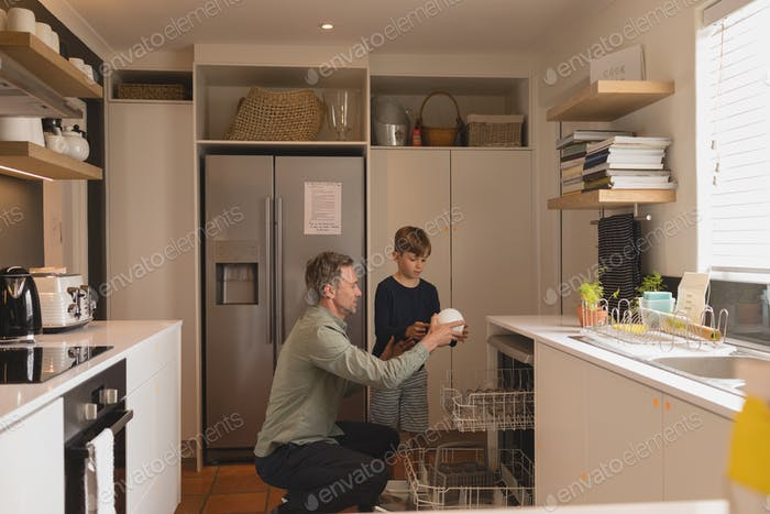 Front view of father and son doing chores together taking out clean dishes out of the dish washer