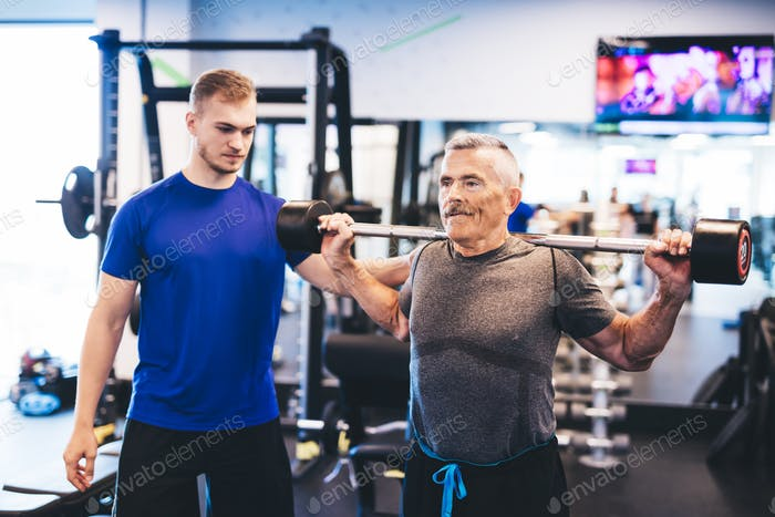 Older man assisting senior man at the gym.