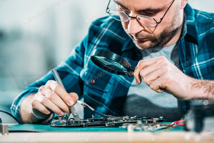 Engineer fixing circuit board looking through magnifying glass